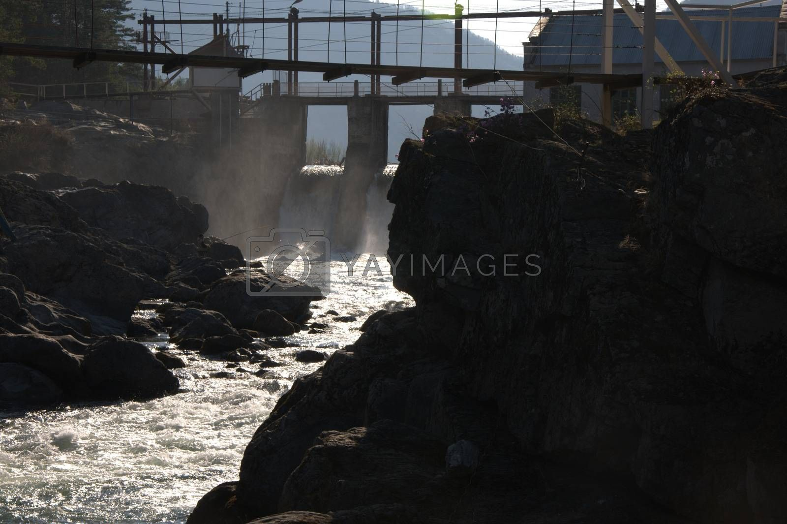 The dam of the old hydroelectric power station and a suspension bridge over a raging mountain river. by Alex Yellow