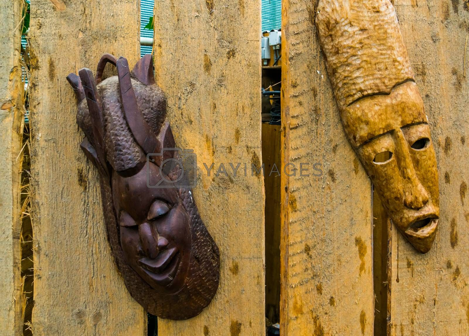 traditional african wooden masks hanging on a wooden fence by charlotte Bleijenberg