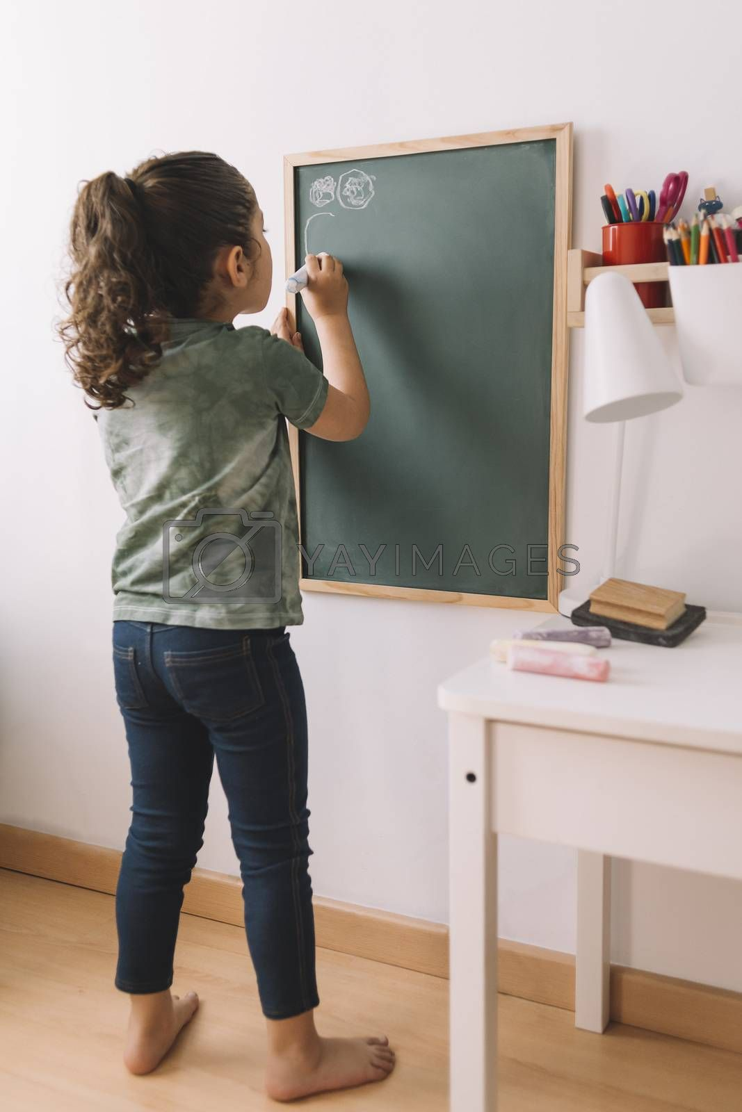 little girl drawing on the blackboard at her room by raulmellado