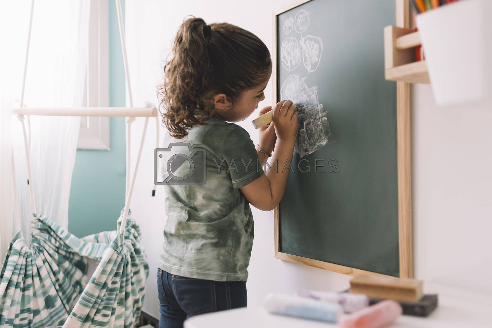 little girl drawing on a blackboard at her room by raulmellado