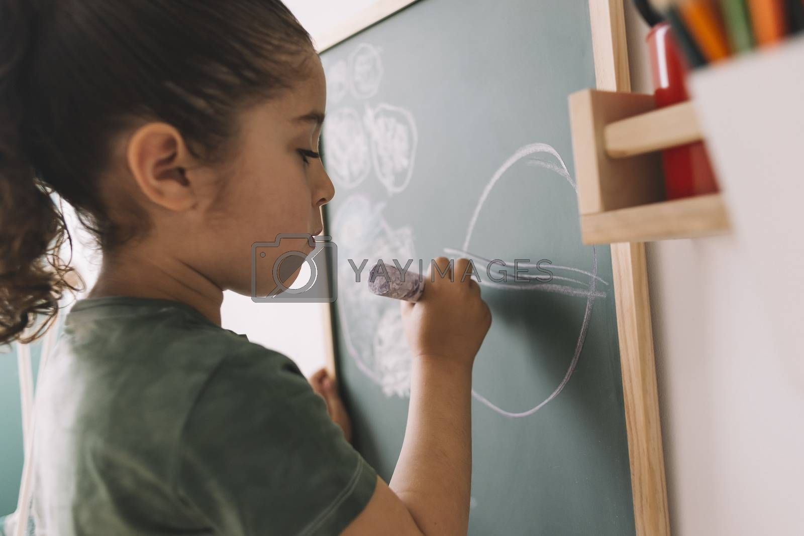little girl drawing on the blackboard by raulmellado