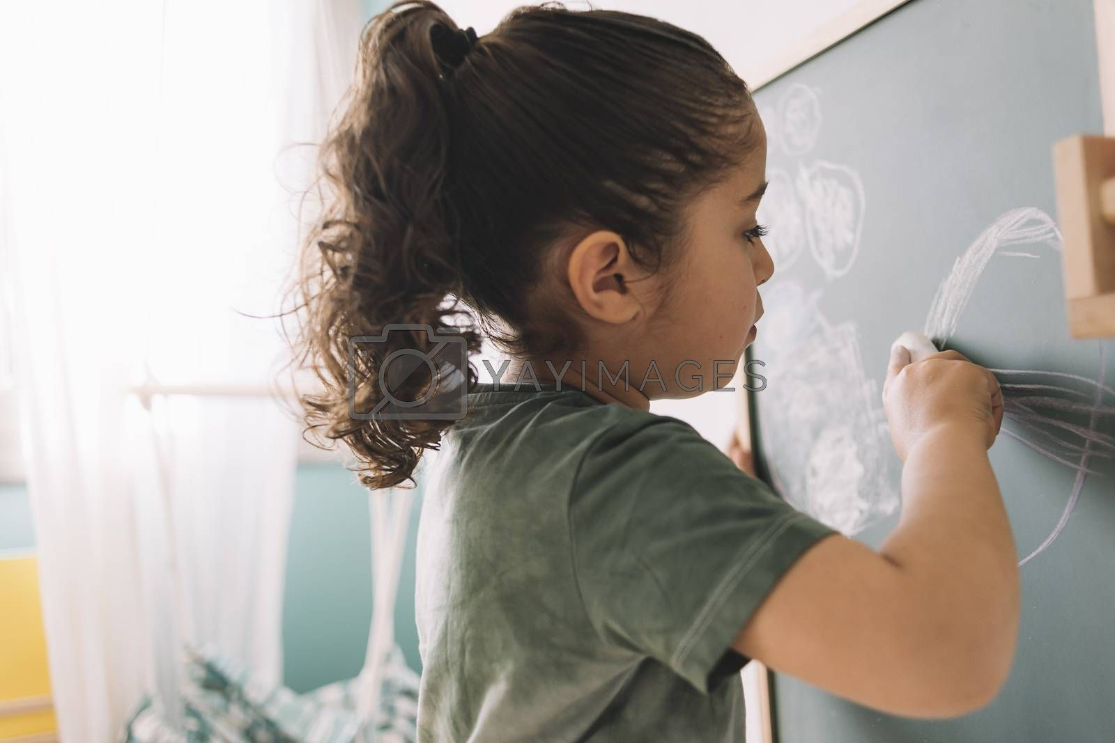 little girl drawing on a blackboard at home by raulmellado