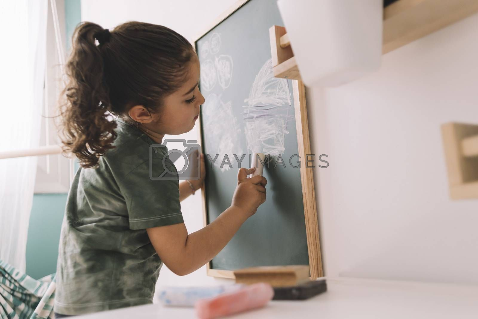 little girl drawing on a chalkboard at her room by raulmellado
