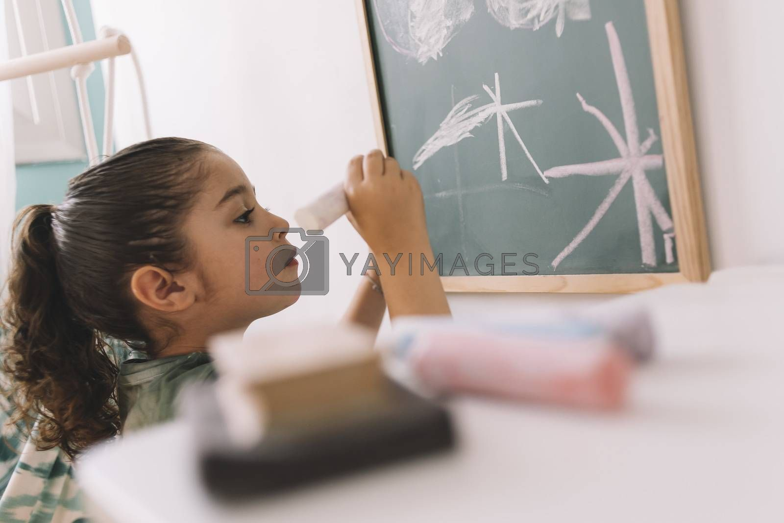 little girl draws focused on the chalkboard by raulmellado