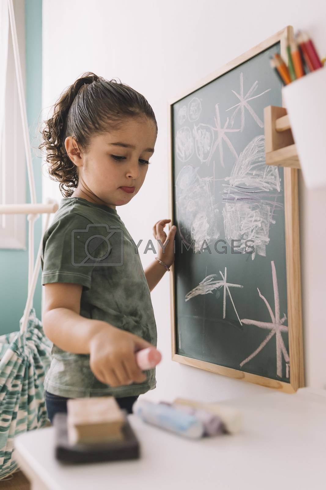 little girl picks up a chalk to draw at home by raulmellado