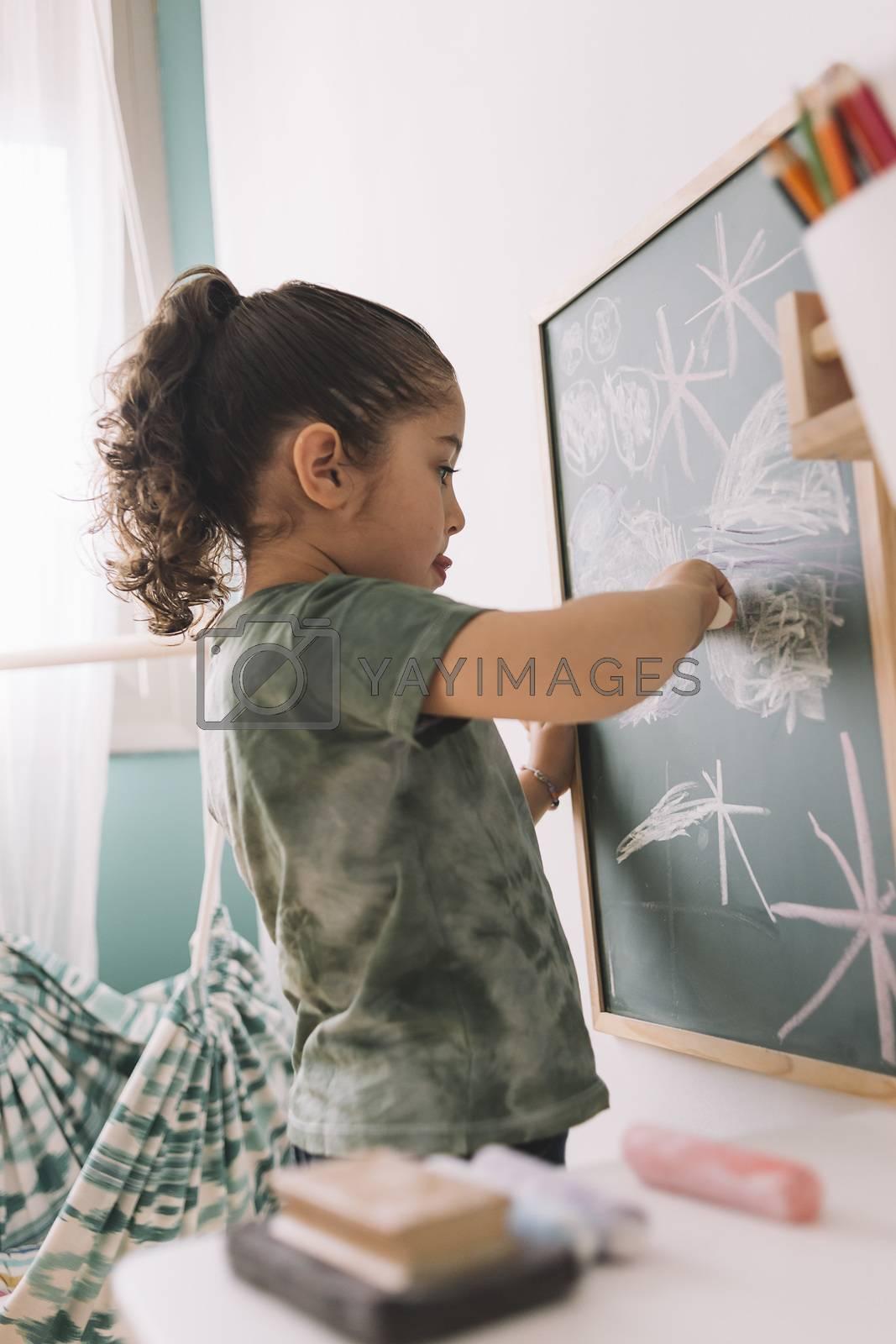 little girl drawing focused on the chalkboard by raulmellado