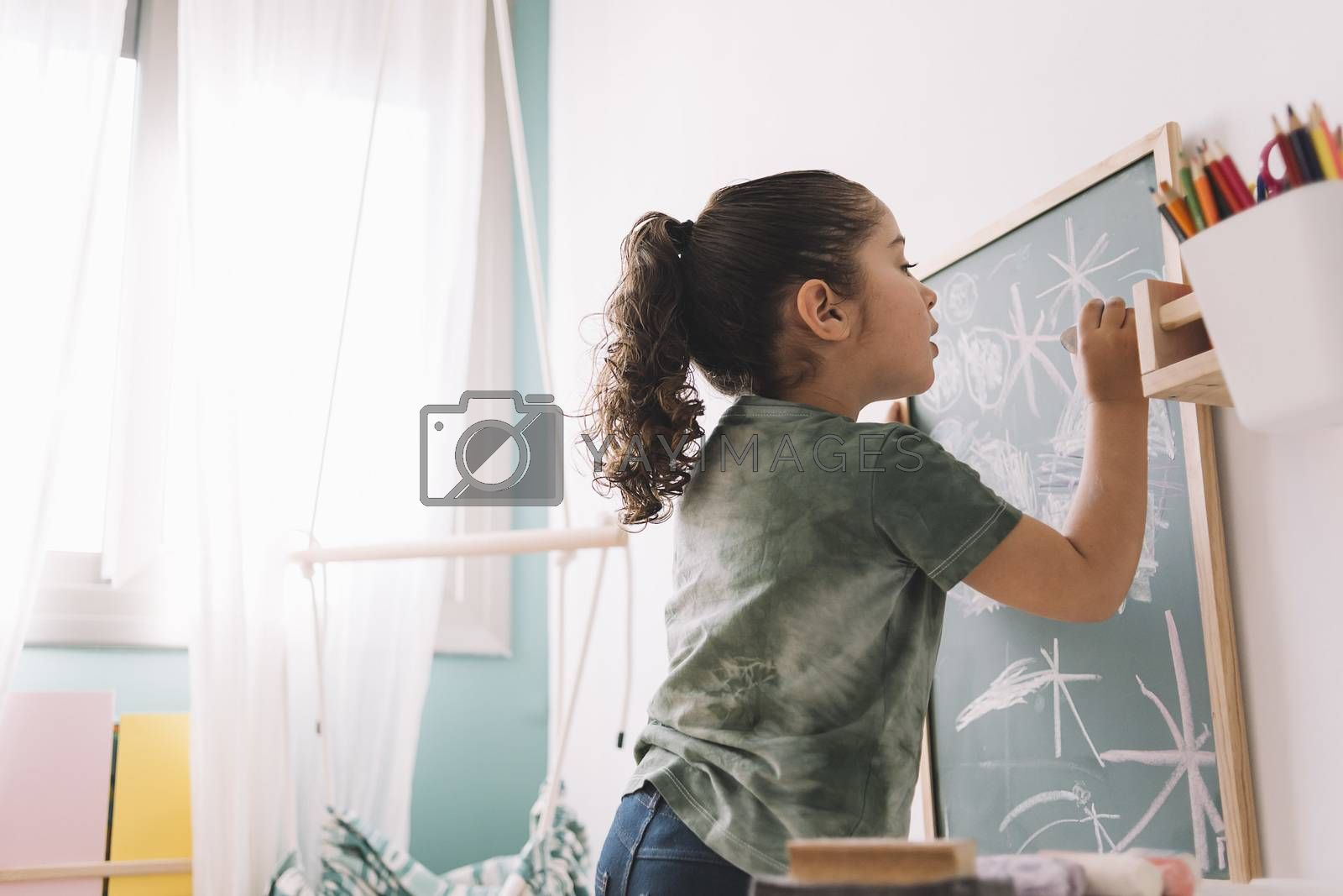 little girl drawing concentrated on the chalkboard by raulmellado