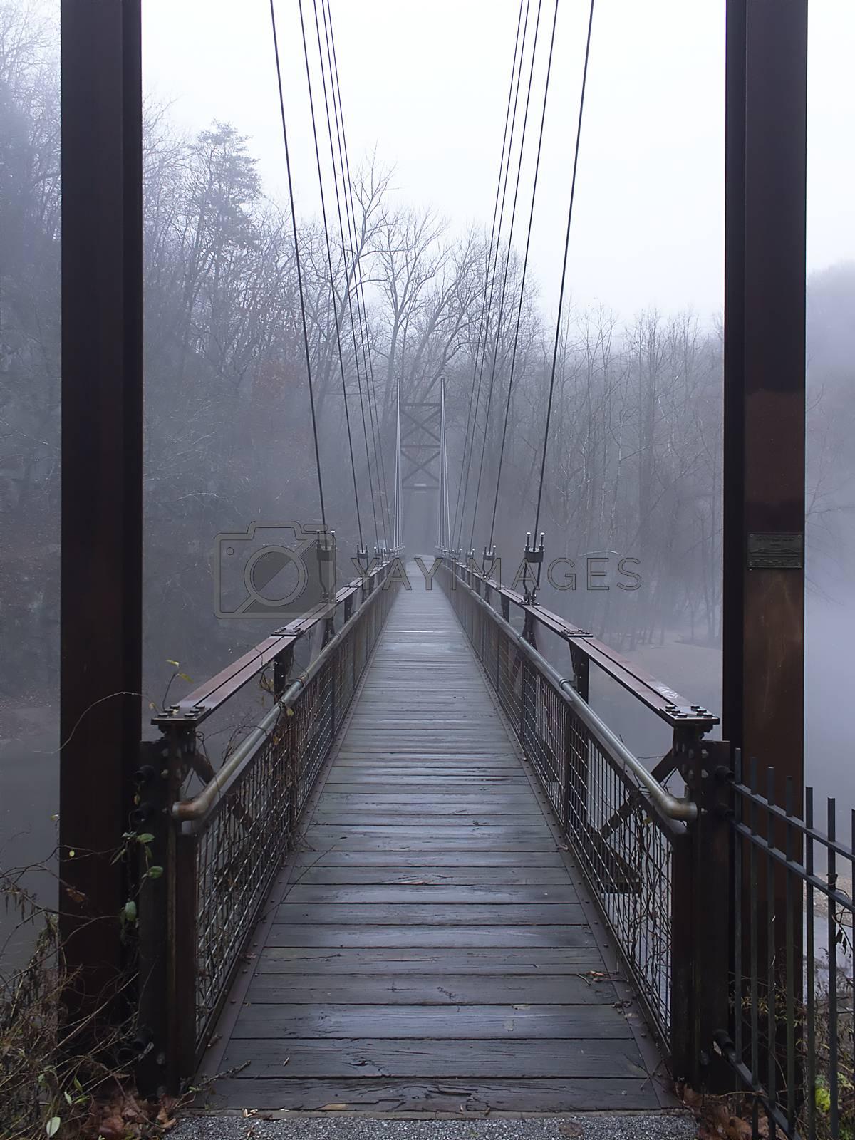 Pedestrian suspension bridge over river by Charlie Floyd