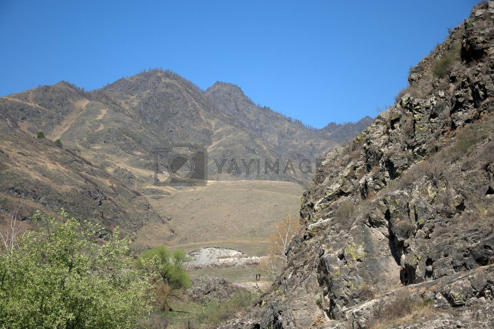 View of the fertile valley surrounded by high mountains under a clear blue sky. by Alex Yellow