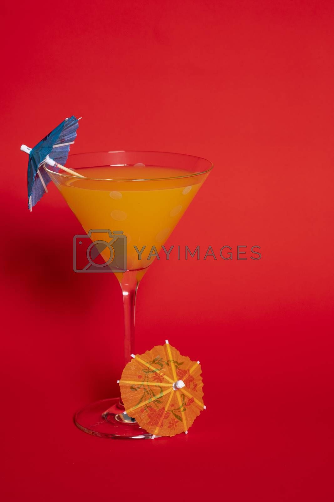 Orange Drink in Martini Glass Against Red by Charlie Floyd