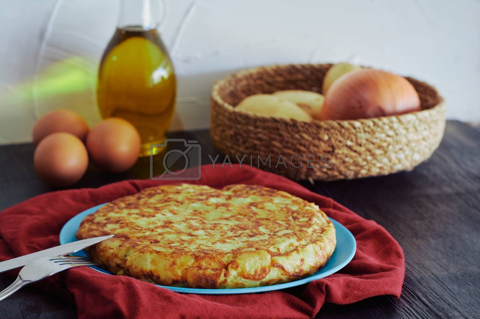 Spanish omelette with potato, egg and onion, accompanied by olive oil
