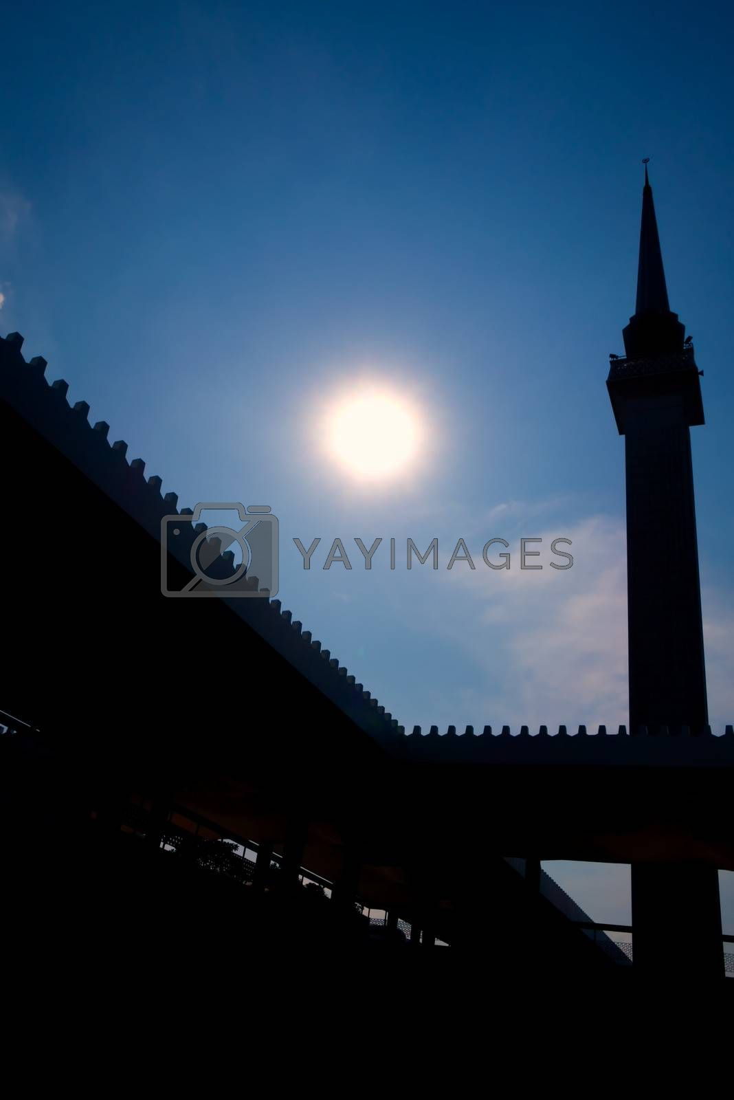 modern minaret against the sun with blue sky background and discreet cloud