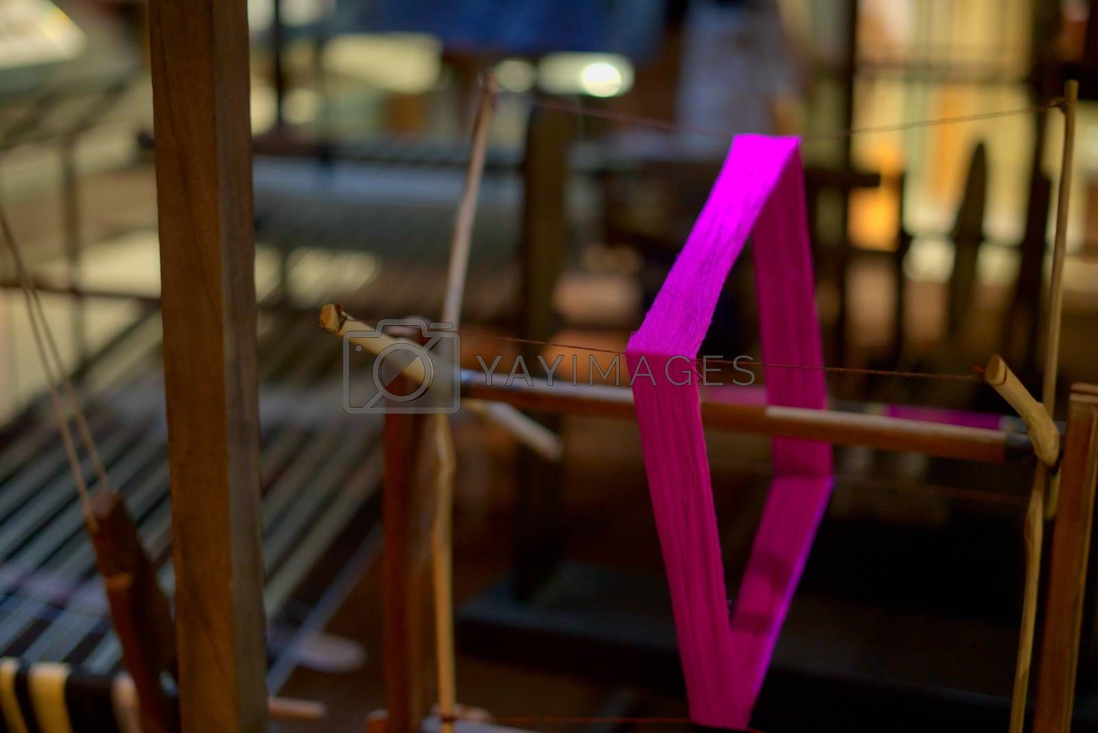 Malaysian traditional textile wooden loom with flashy spinning purple thread in focus