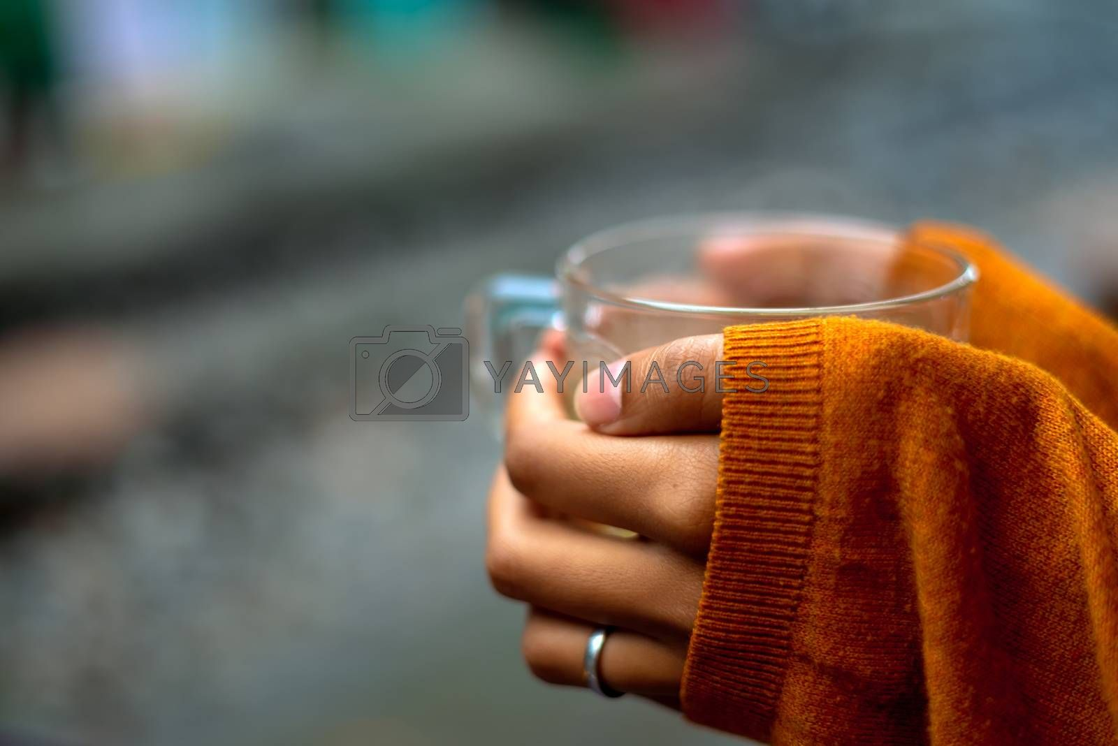 holding a cup of tea by rails waiting for the train with orange pullover covering hands by half