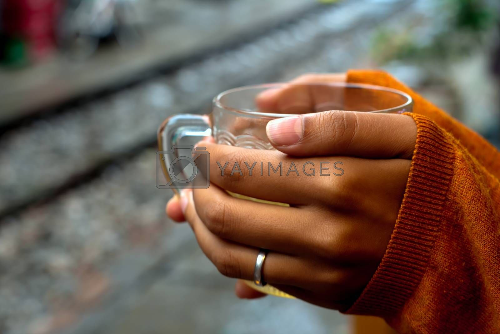 holding a cup of tea by rails waiting for the train with orange pullover covering hands by a third