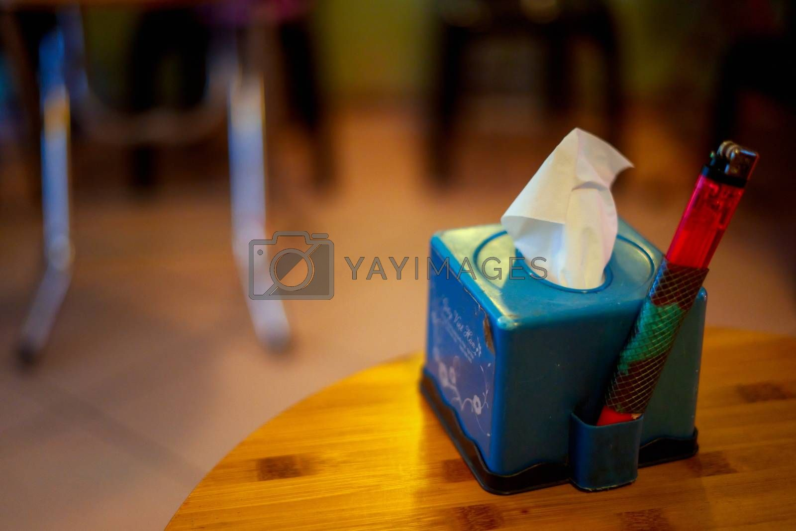blue plastic tissue box with double lighter held on the side on a table inside a bar