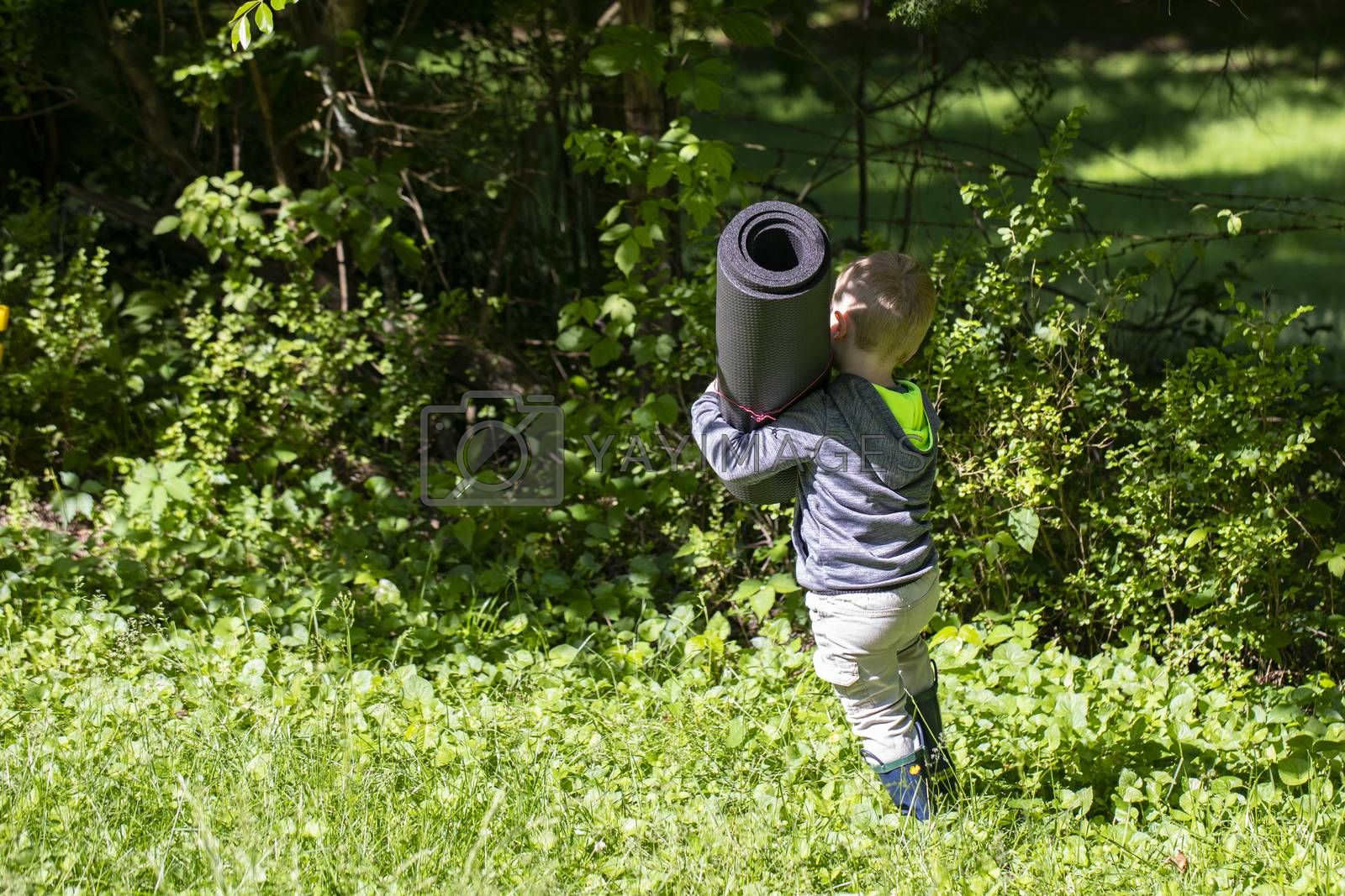 Male toddler carries rolled up mat through the grass.