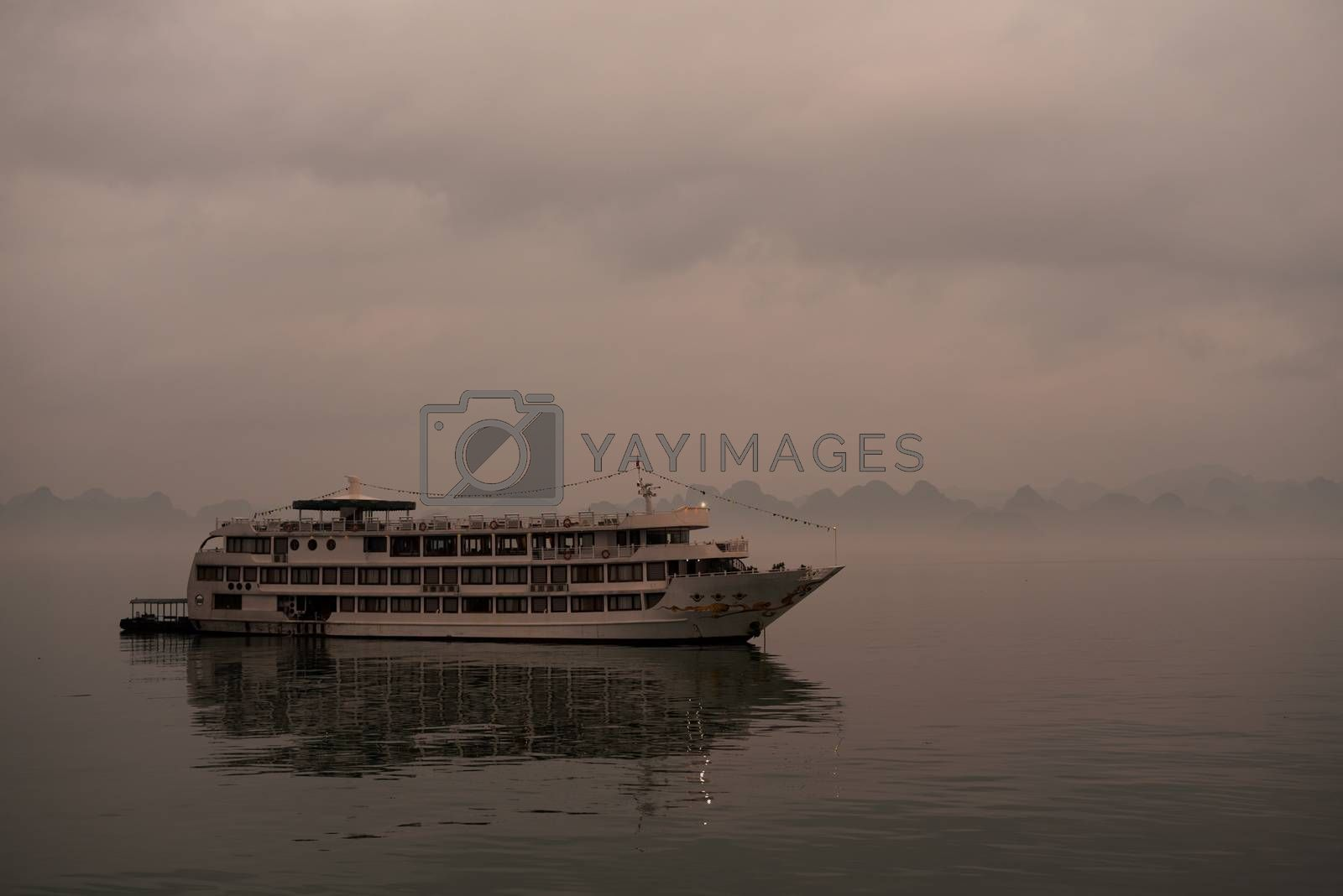 one cruise boat on Halong bay cloudy early light with myst and reflection