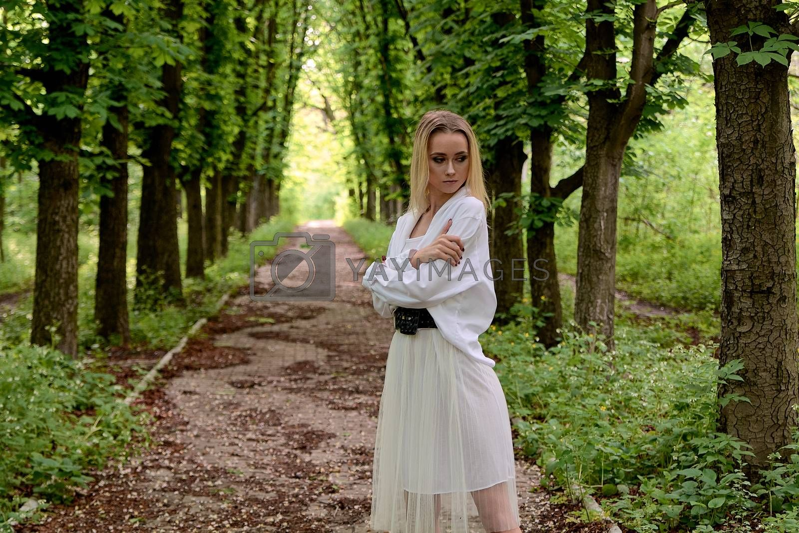 Blonde woman walks alone along the chestnut alley in the city park. Young woman modern portrait. by nixrenas