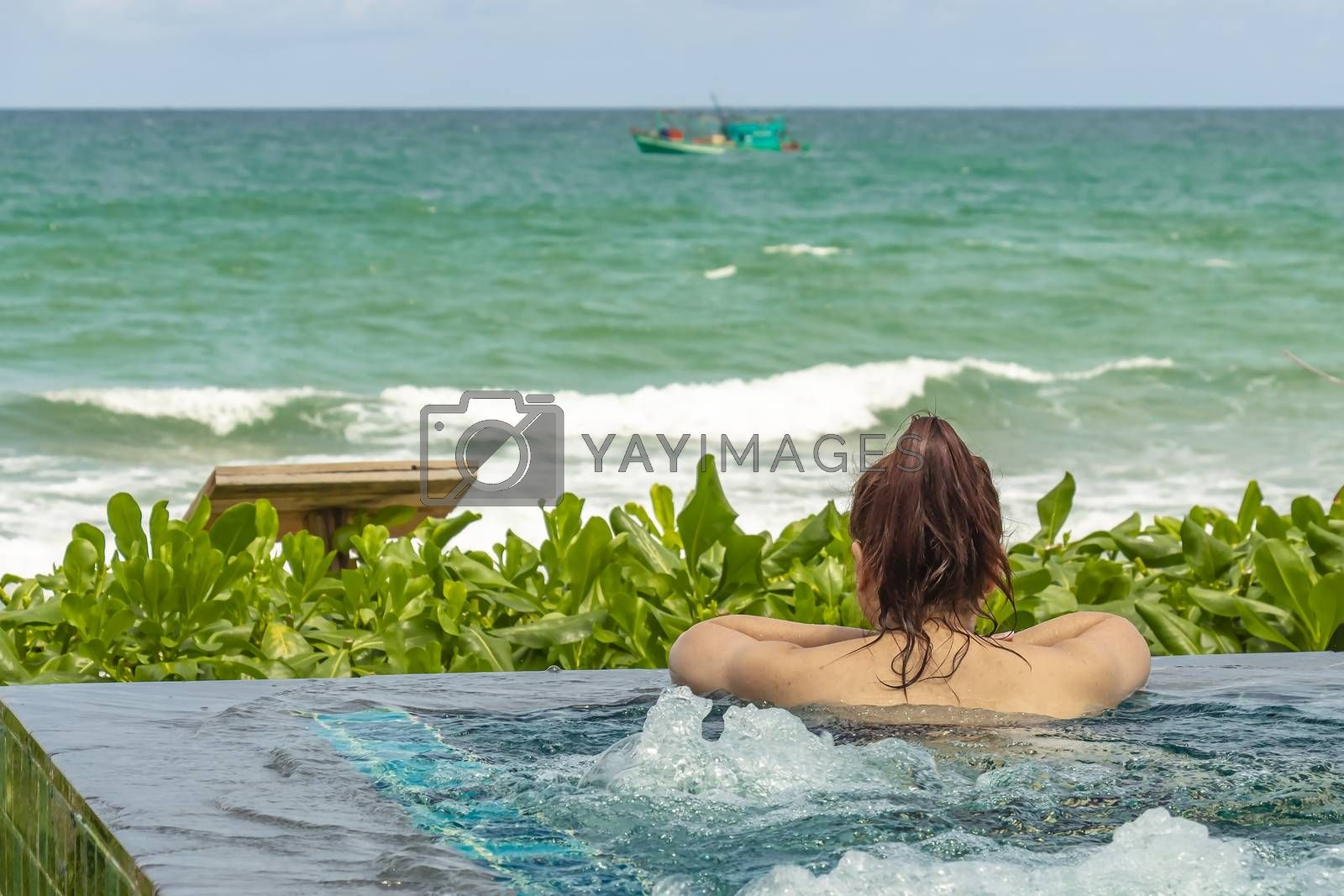 Female in a beach resort swimming pool looking towards the open sea