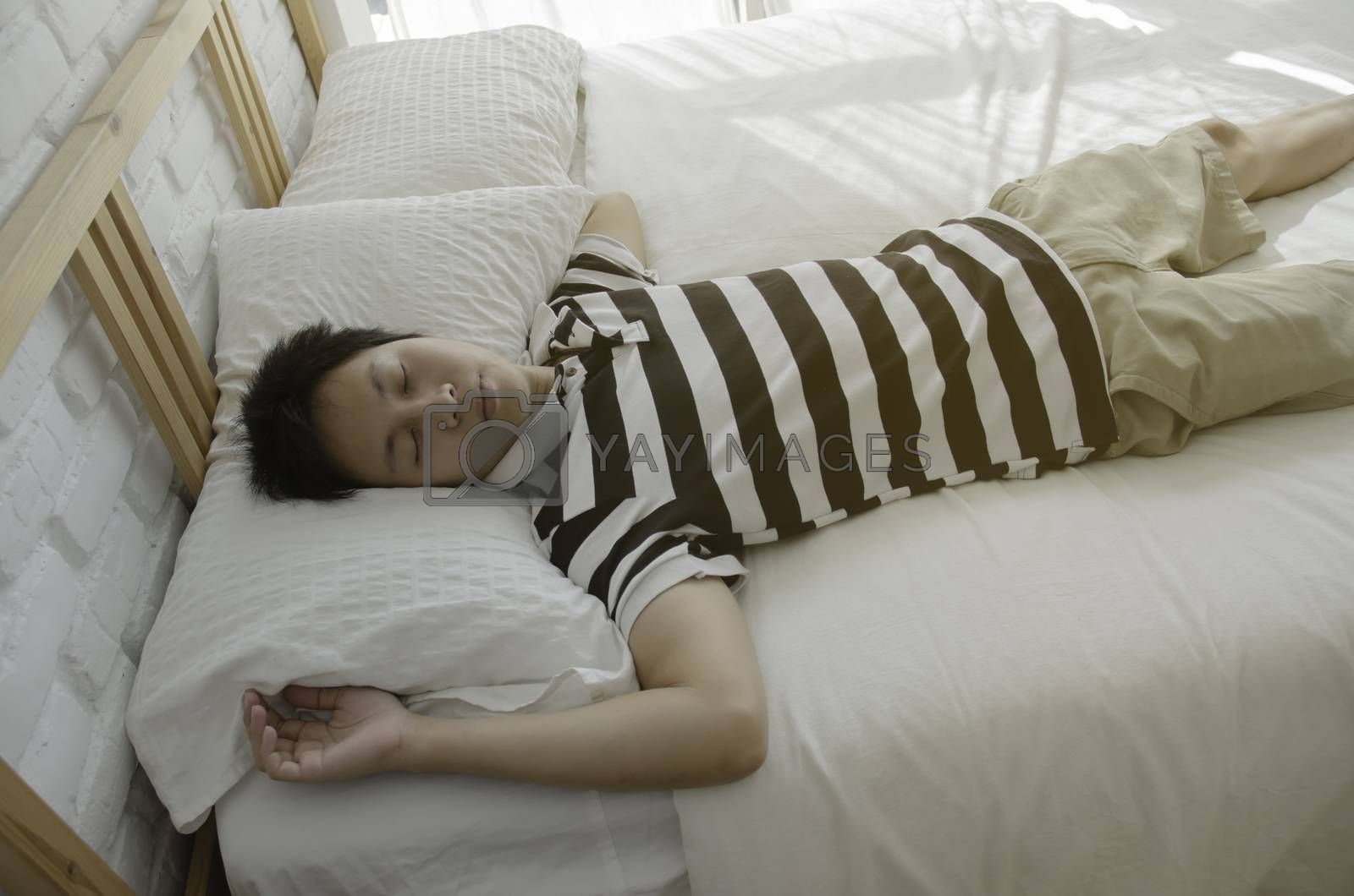 Asian guy sleeping in a white bedroom.Man sleeps well in bed in a white bedroom. Relax in the room.He was sleeping in the morning with sunlight. Warm.He man kneeling bent on the bed.