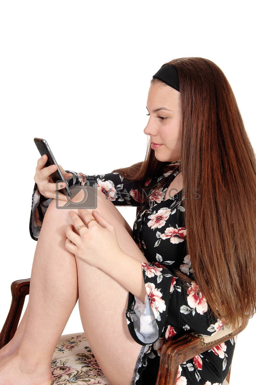 Pretty teen girl sitting on a chair looking at her cellphone by feierabend