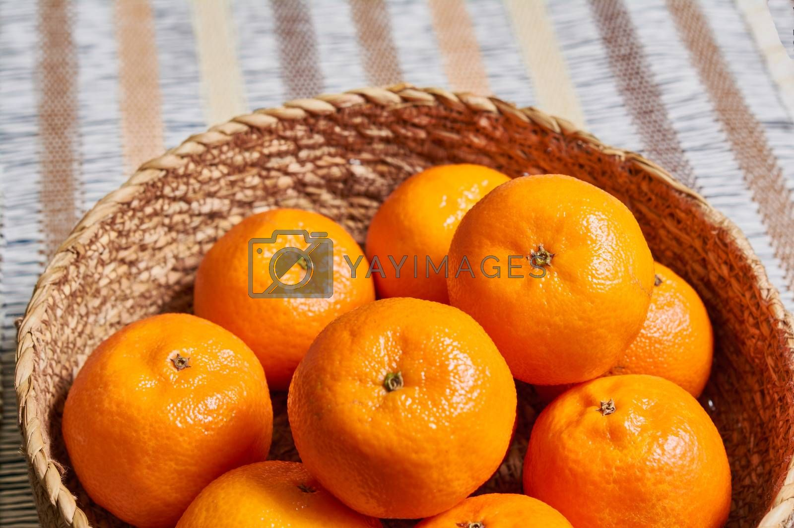 Royalty free image of tangerine basket with artisan tablecloth background by Prf_photo