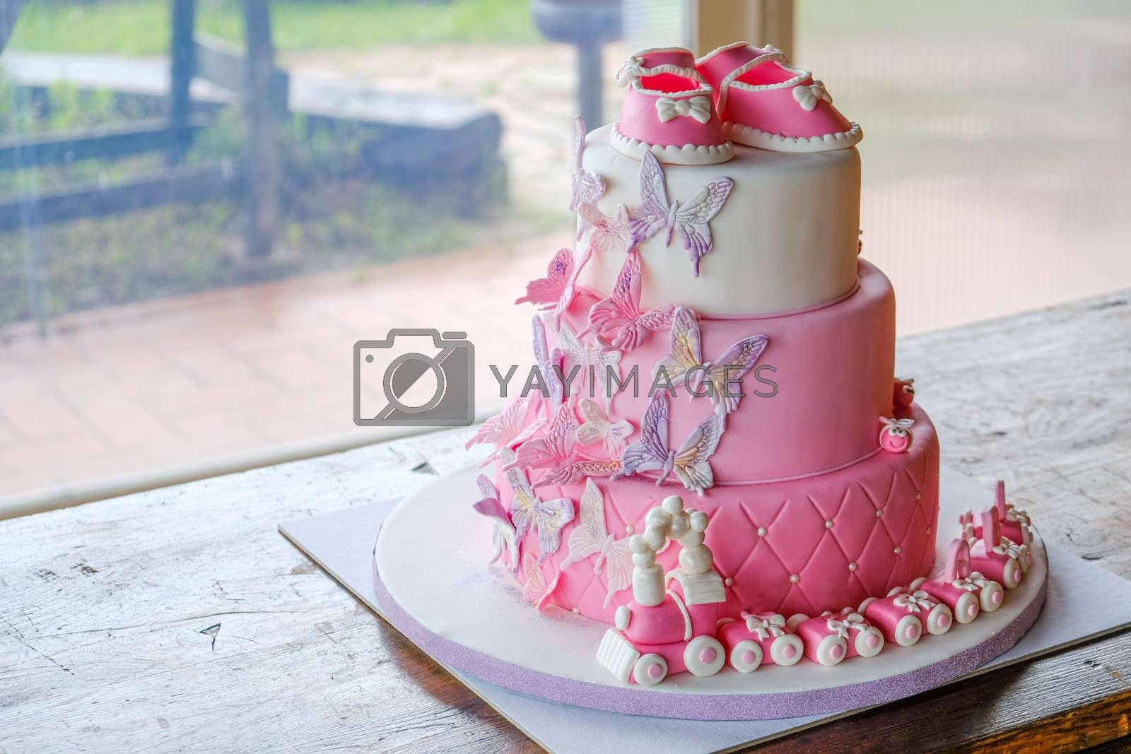 fist cake for a little baby girl birthday for celebrating baptism - pink sugarpaste layered cake design no people .