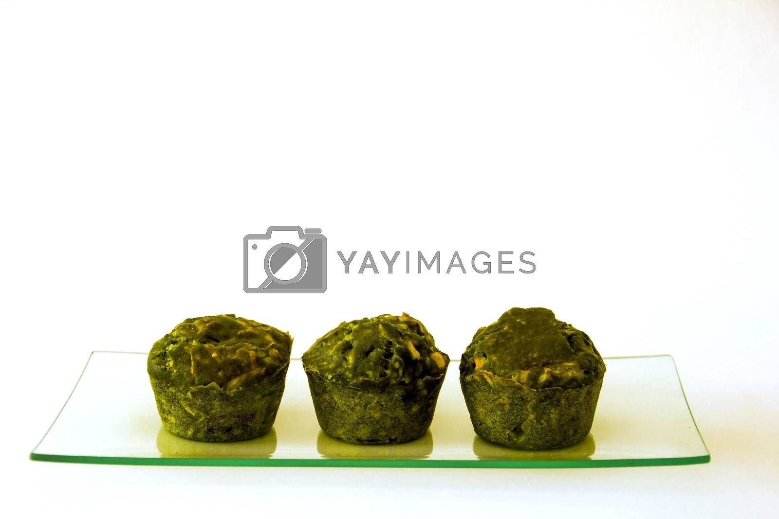 Green muffins on a glass tray with white background