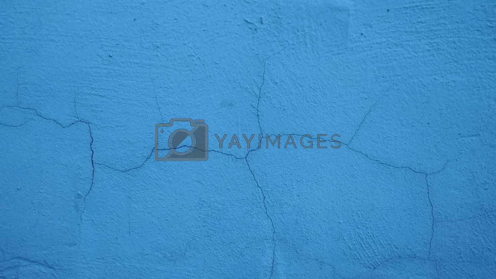 The crack on the plastered wall painted blue. Background, texture.