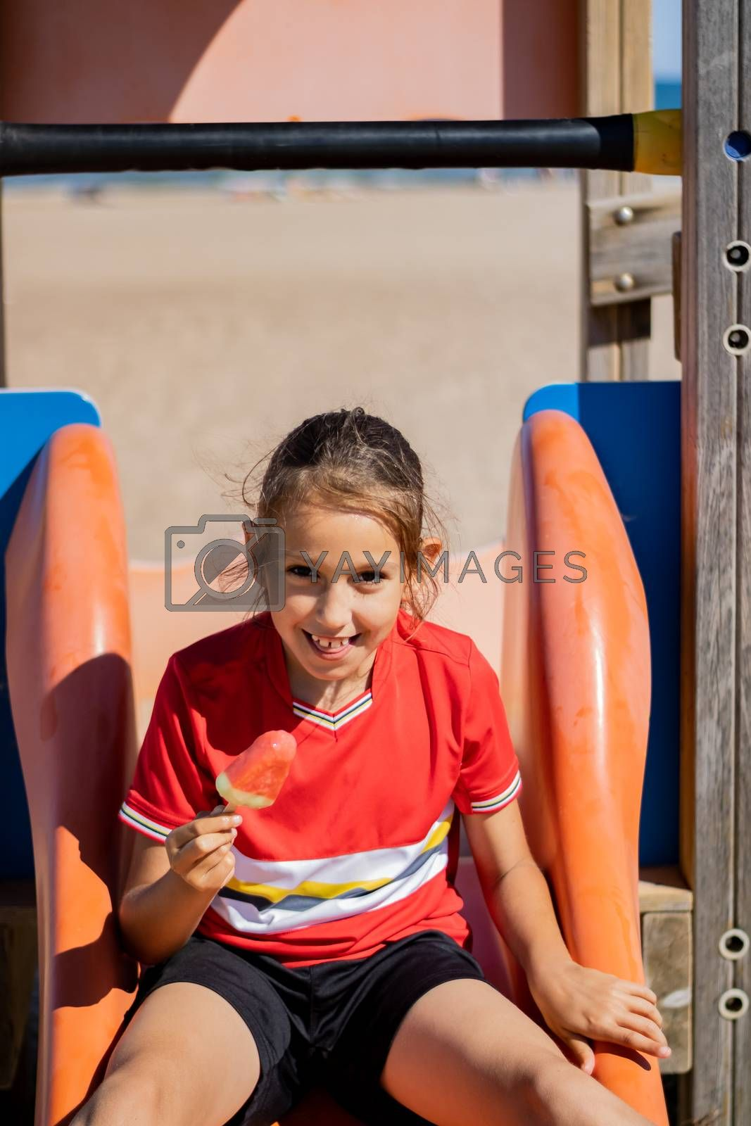 Little girl eating an ice cream on the beach