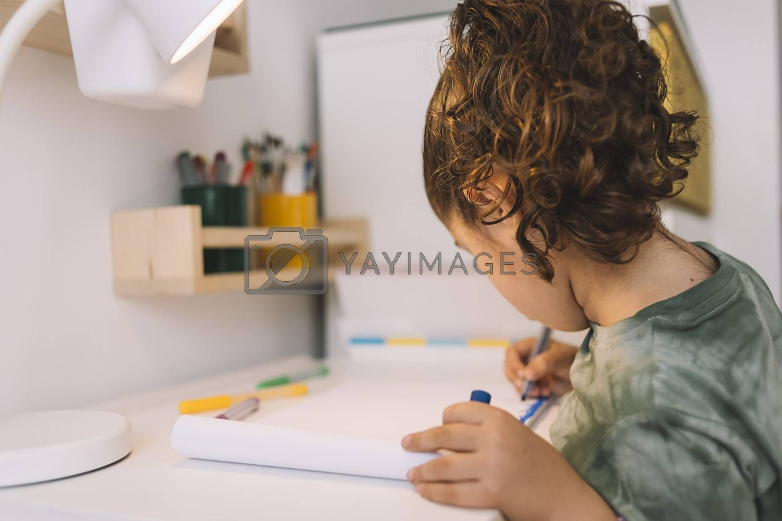 little girl draws at home with color markers, she is drawing on the desk in her room