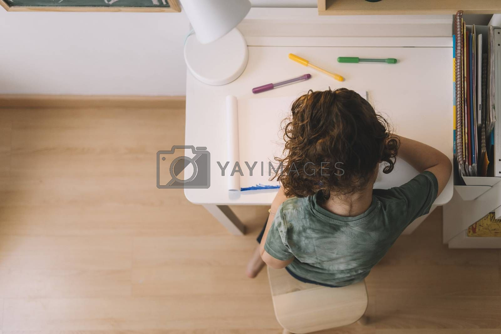 top view of a little girl draws at home with color markers, she is drawing on the table in her room, copy space for text