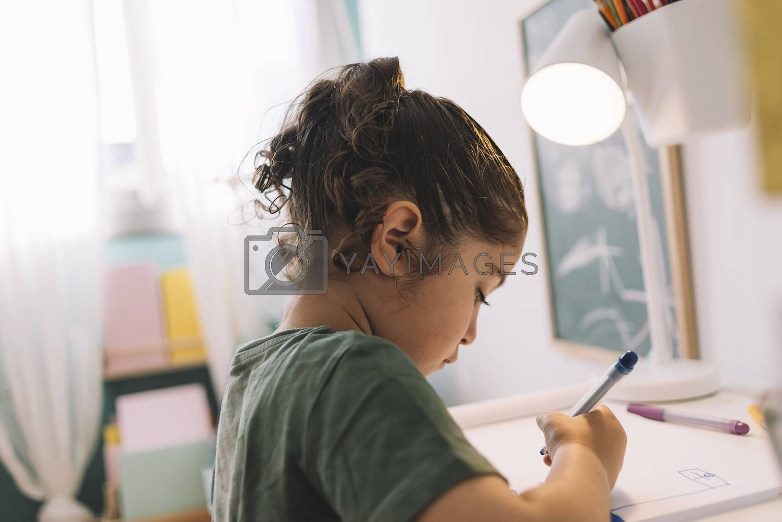 little girl draws concentrated at home with color markers, she is drawing on the table in her room