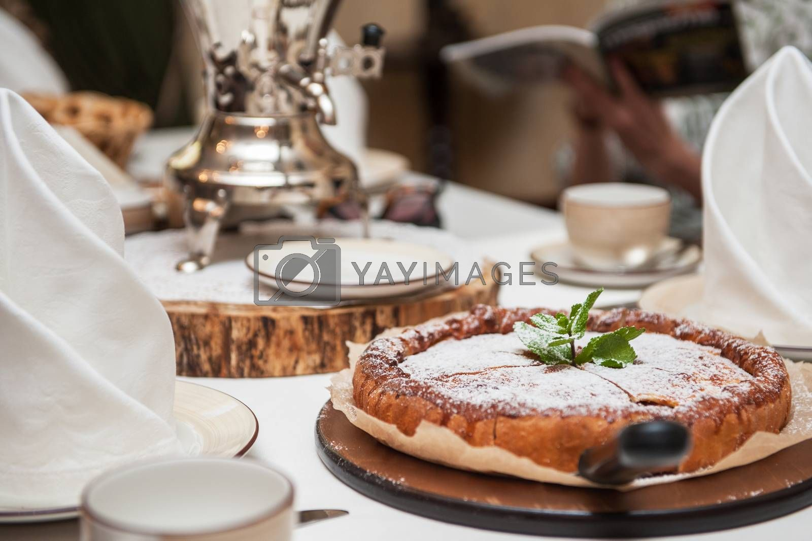 Apples pie with samovar on the served table