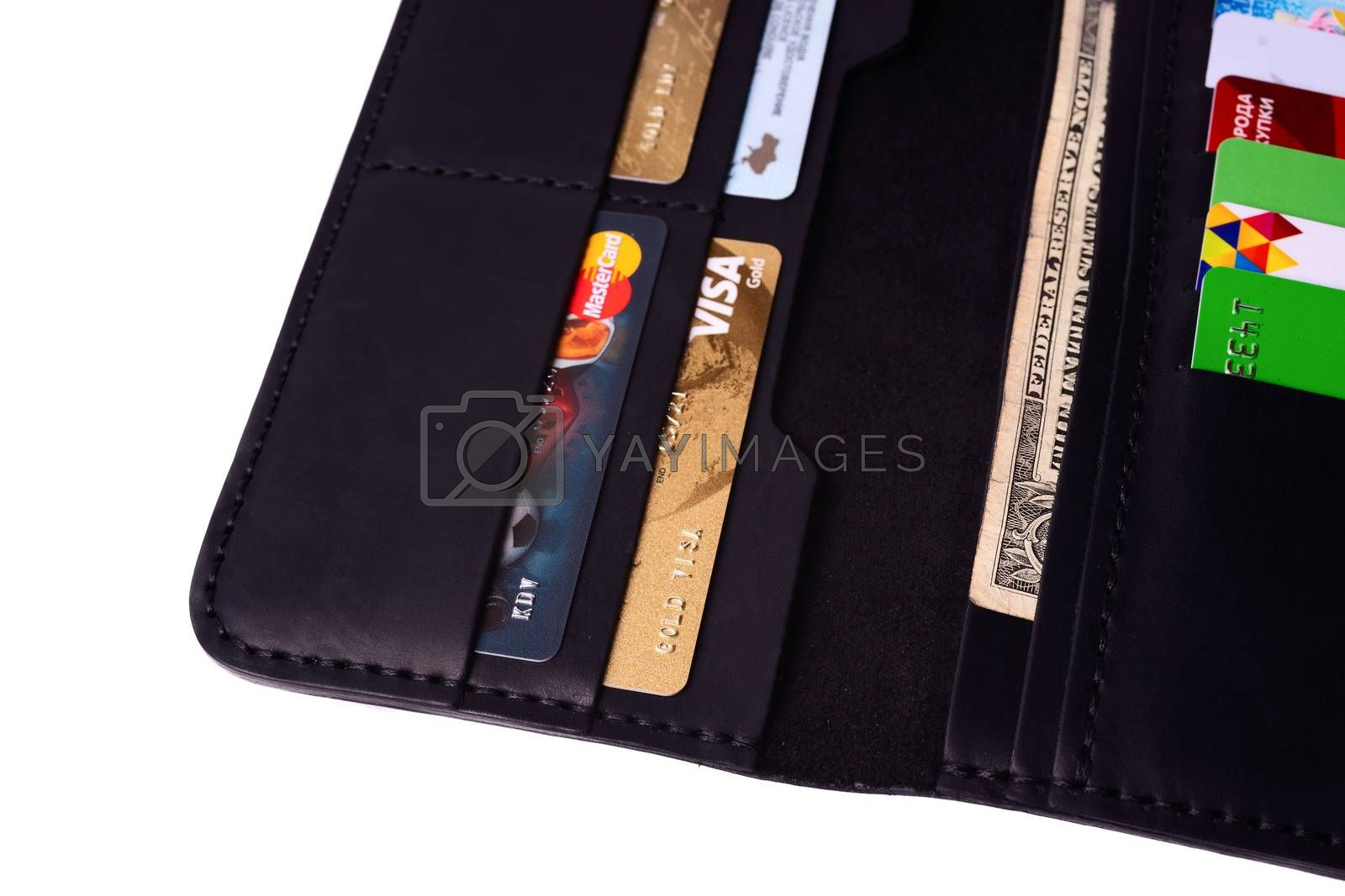 24.01.2019 Ukraine, Kyiv. A part of handmade black leather wallet isolated on white background closeup. A lot of plastic cards in purse pockets. Editorial use only.
