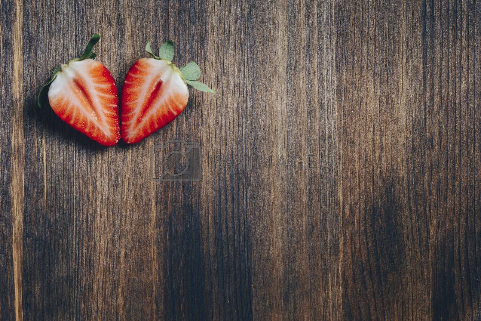 couple strawberry slice cut in half on wooden table in rustic style, healthy sweet food, vitamins and fruity concept. Top view, copy space for text