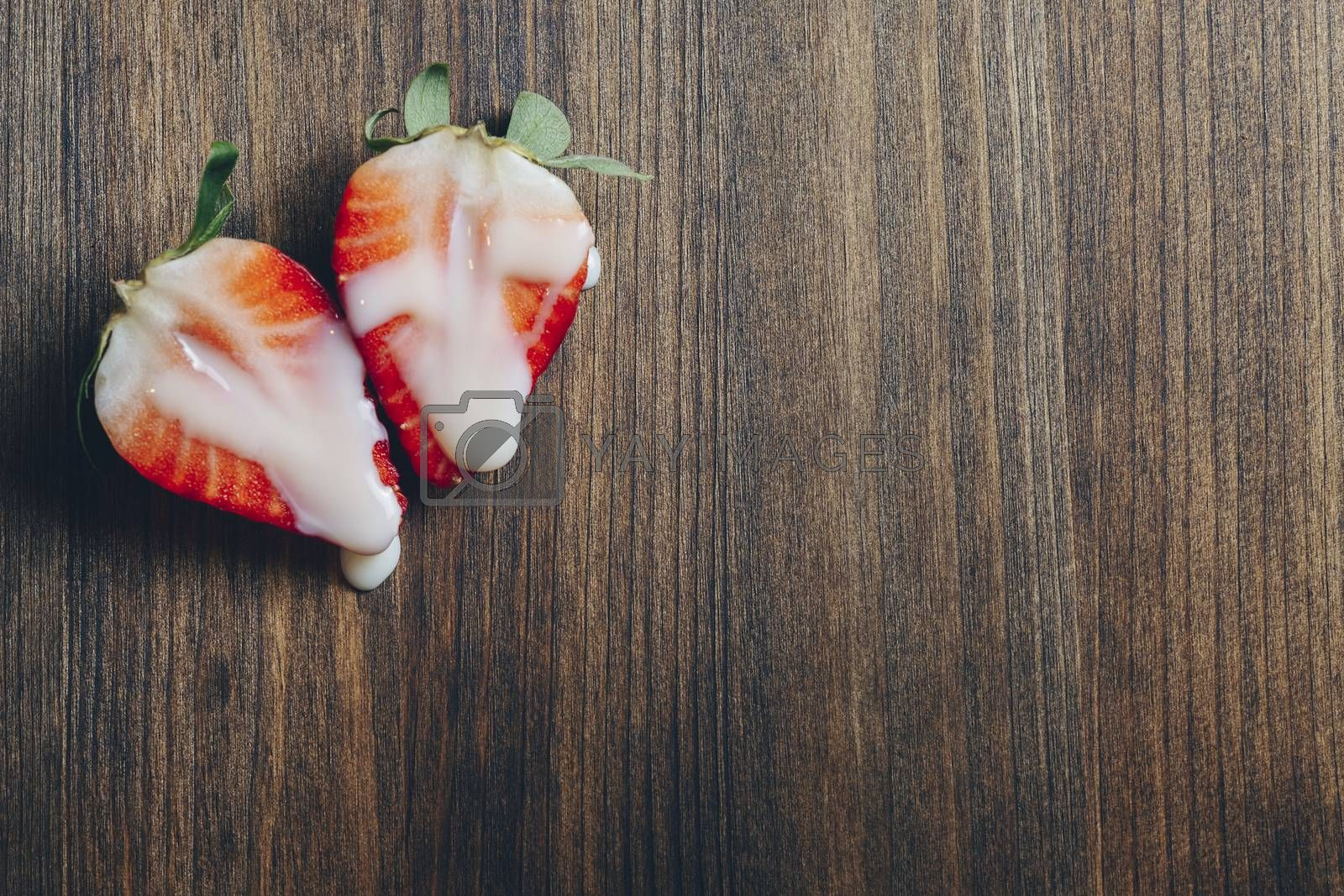 metaphor of sex with strawberries and milk on a wooden table, top view, copy space for text