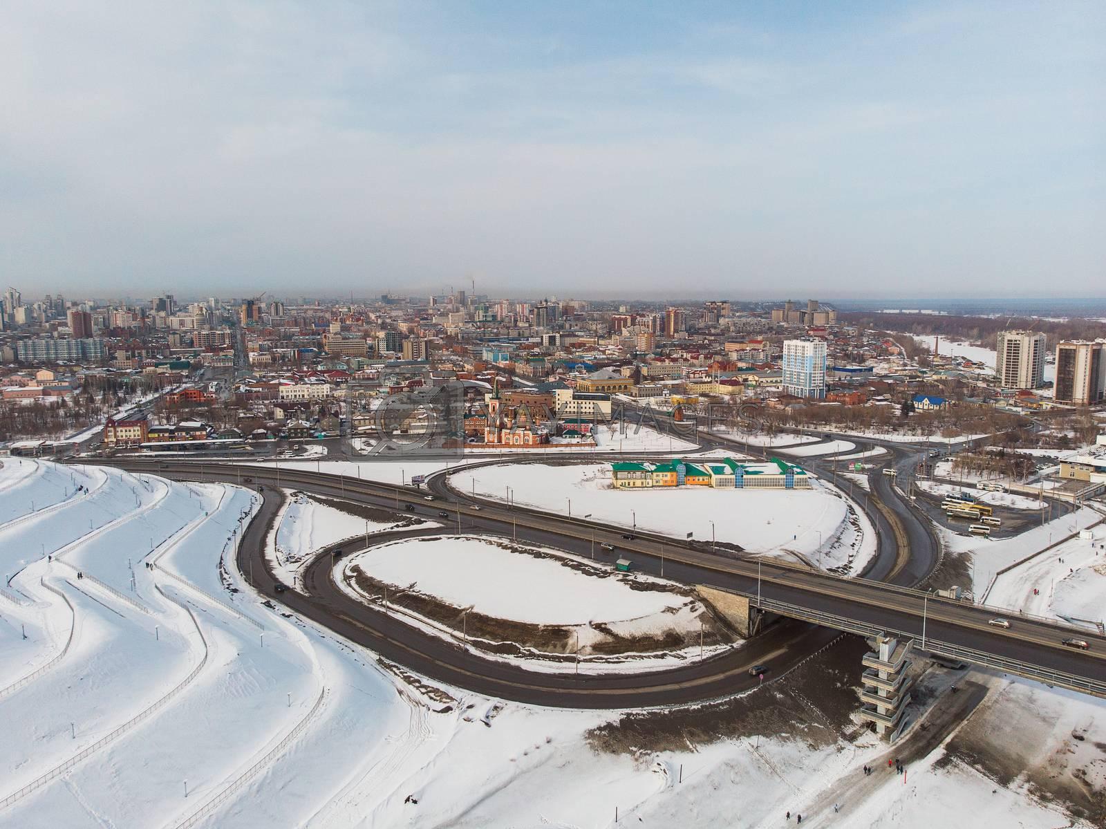 Aerial shot of bridge and car driving on the bridge, winter sunny day in Barnaul, Siberia, Russia