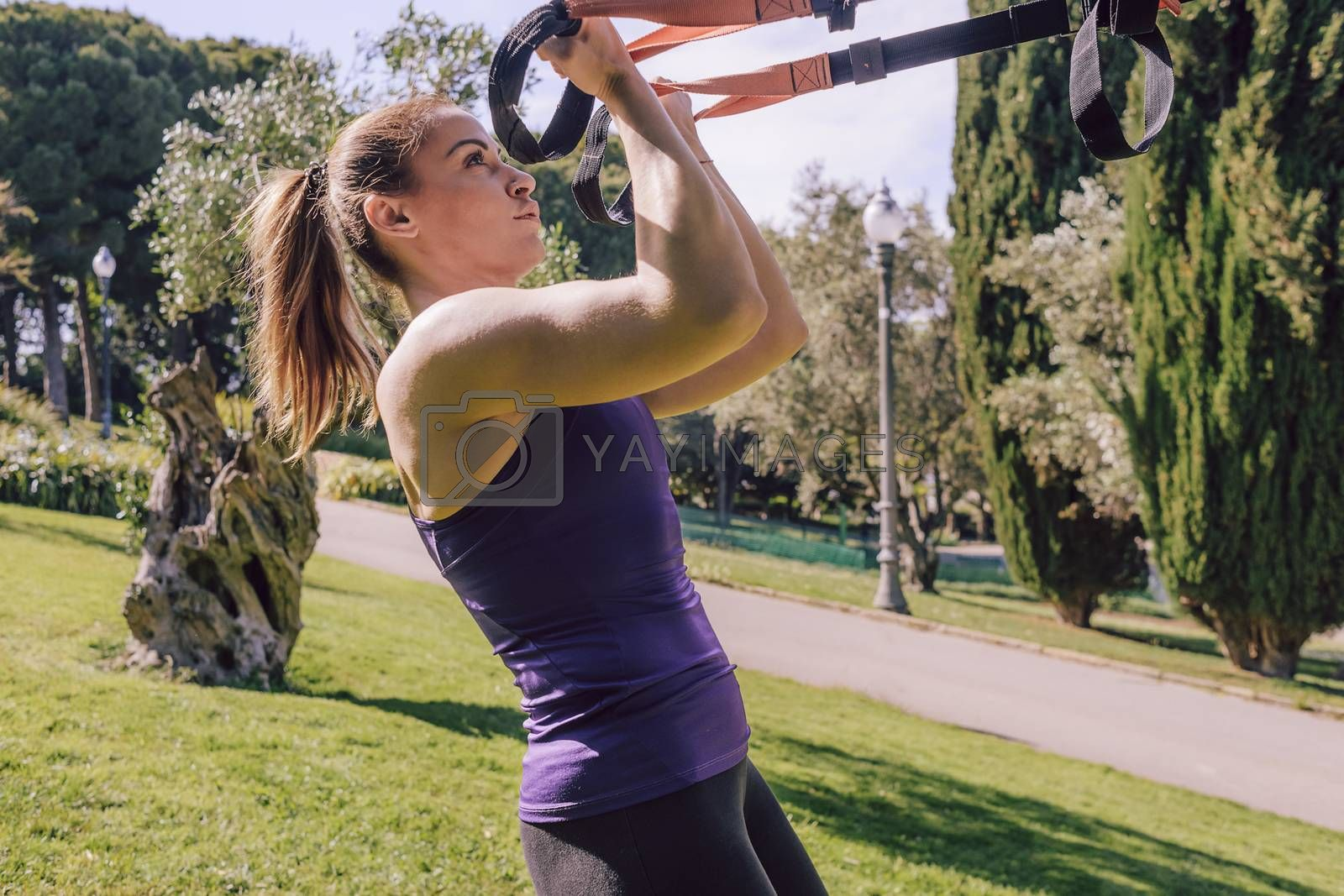 strong young woman training biceps with fitness suspension straps, during functional workout in a outdoor park