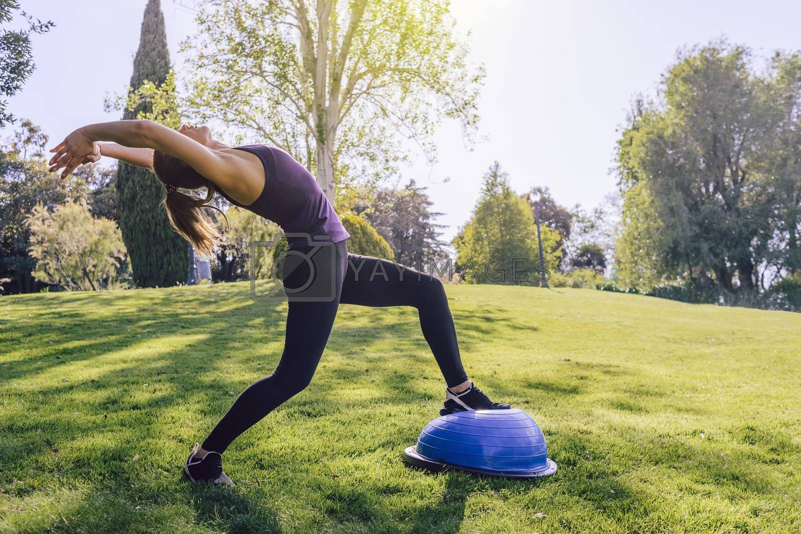 healthy young woman doing stretching yoga workout on the grass on a sunny day, she is outdoors in a park at the morning