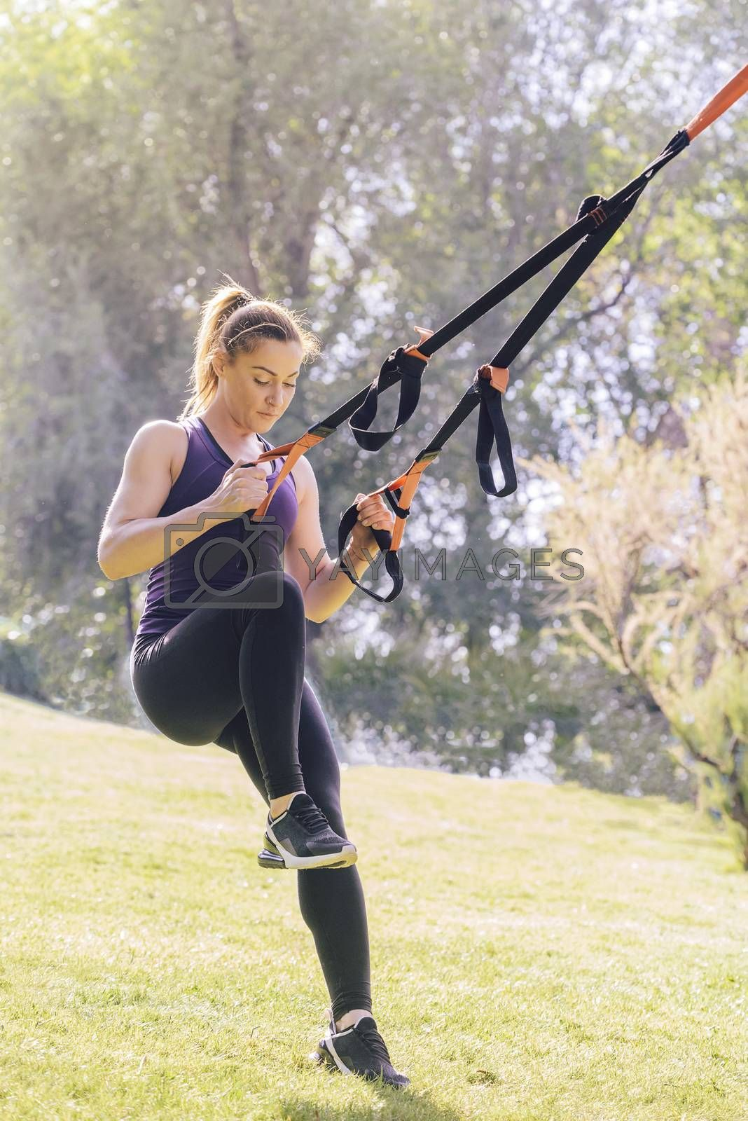 vertical photo of a strong young woman training with fitness suspension straps, during functional workout in a sunny outdoor park at the morning