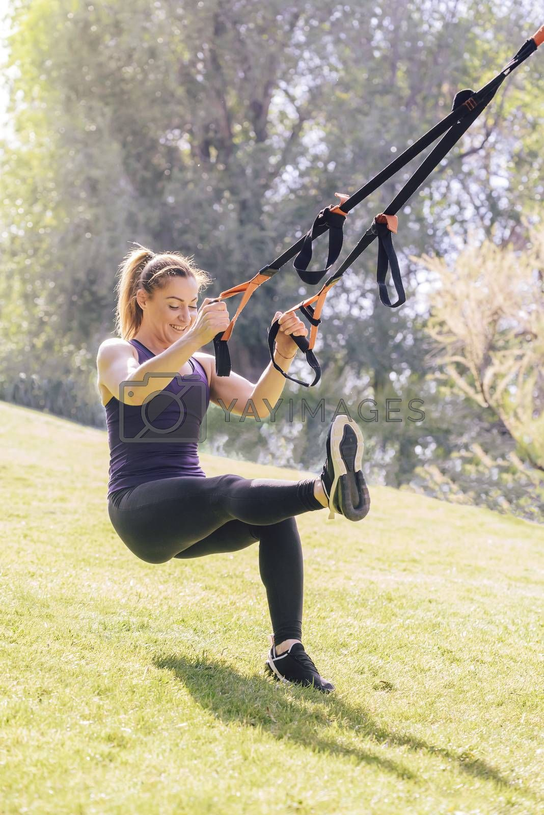 vertical photo of a strong young woman that smiles training with fitness suspension straps, during functional workout in a sunny outdoor park at the morning