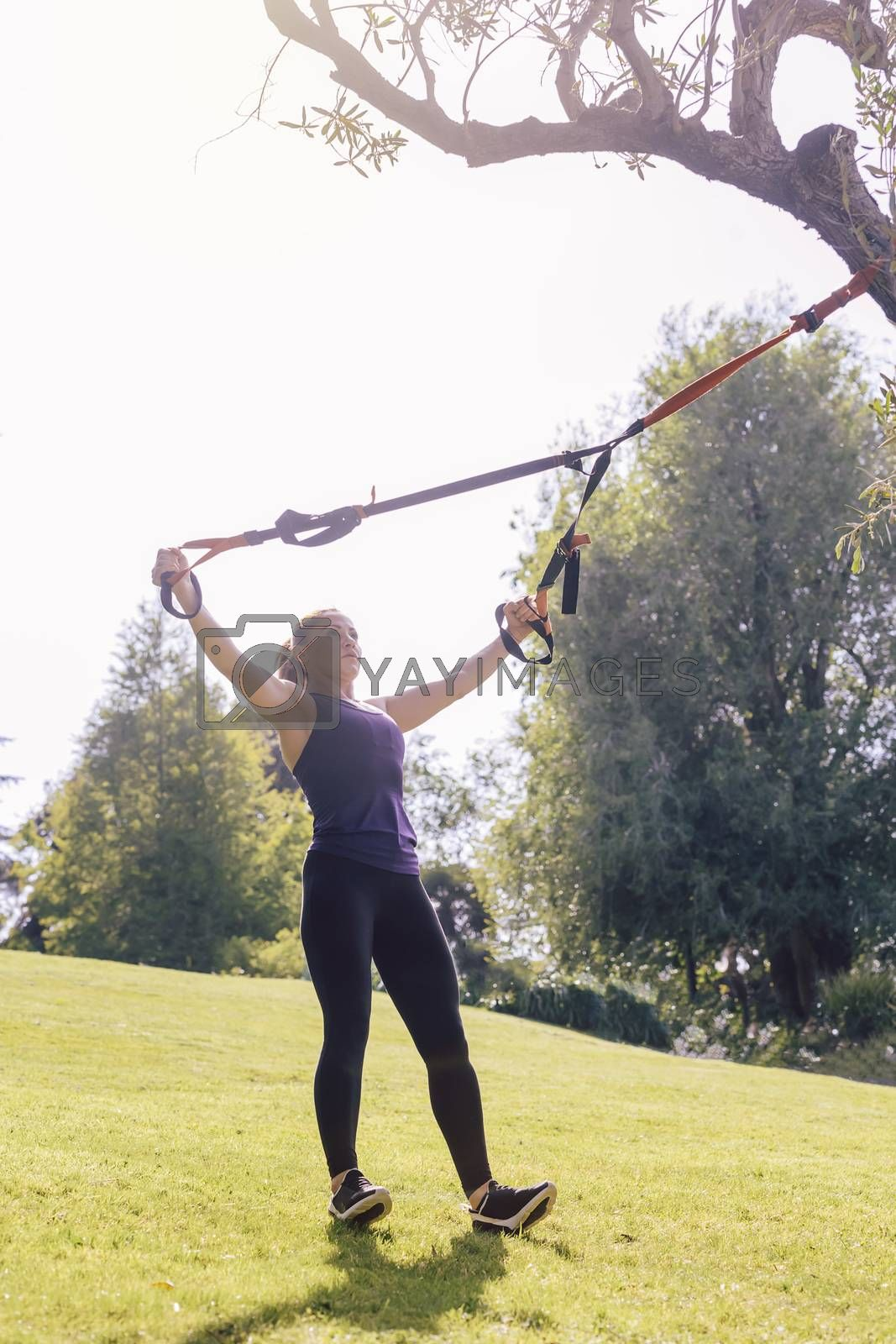 vertical photo of an athletic young woman training with fitness suspension straps, during functional workout in a sunny outdoor park in the morning
