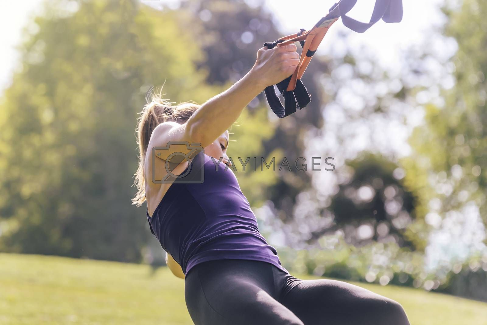 athletic fitness woman training with suspension straps, during functional workout in a sunny outdoor park in the morning