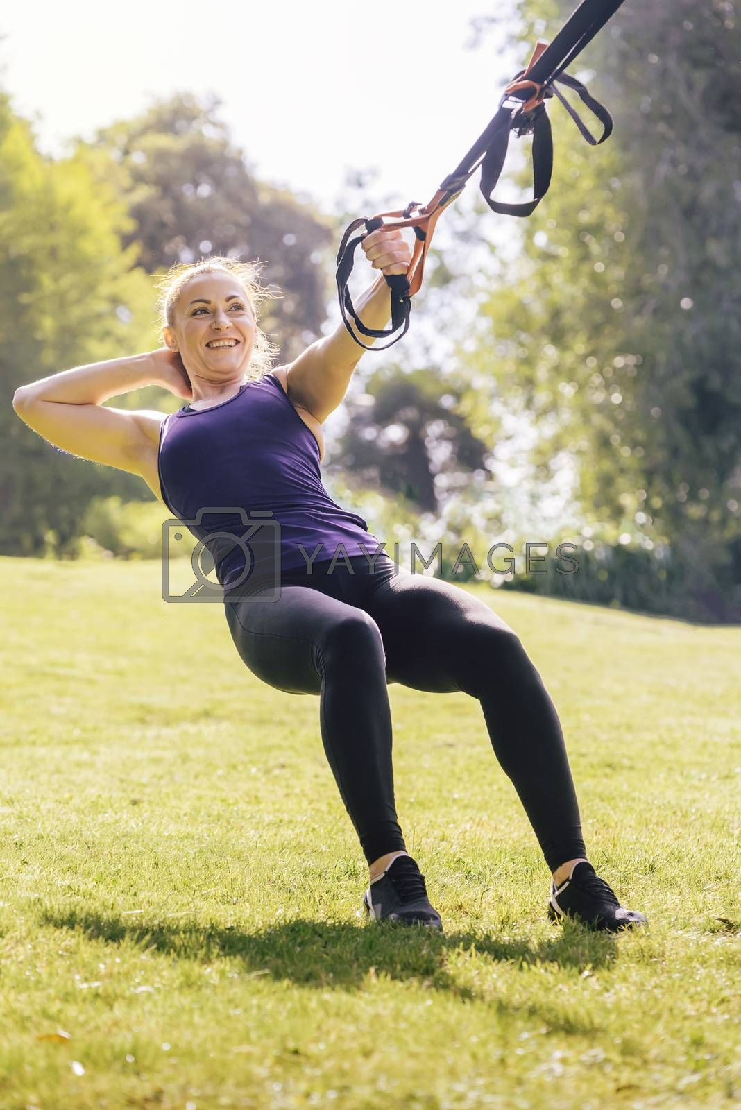 vertical photo of an athletic fitness woman that smiles training with suspension straps, during functional workout in a sunny outdoor park in the morning