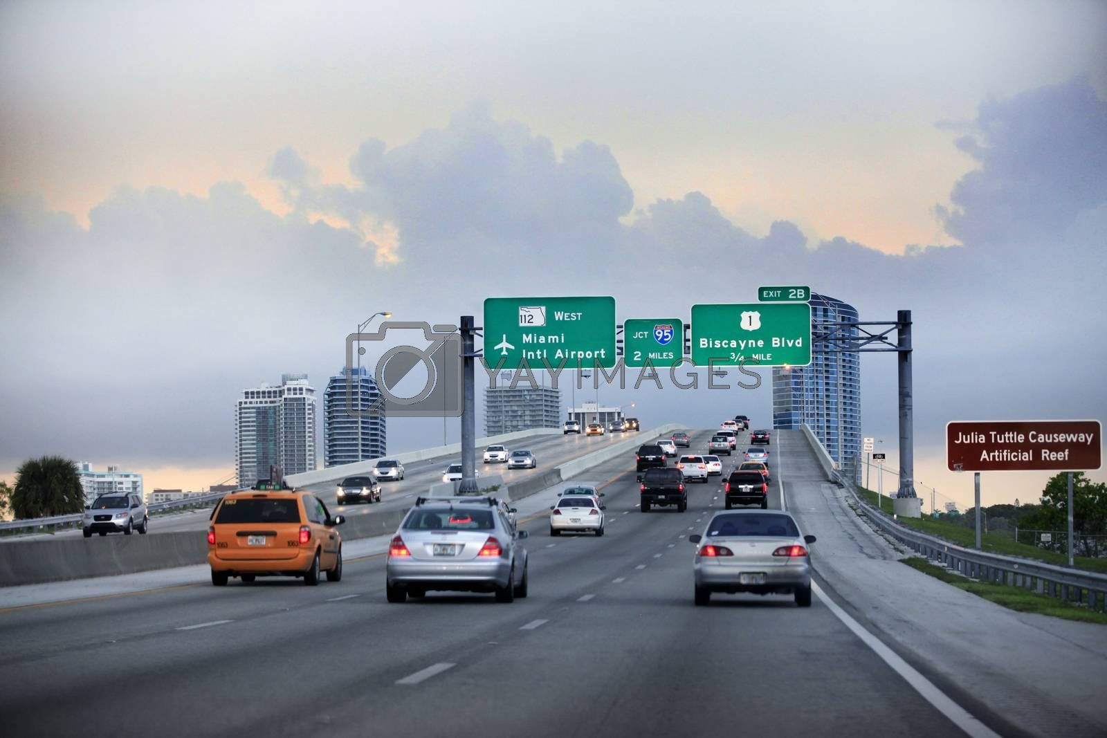 Miami, FL, USA - May 12, 2013: Evening traffic on highway, Miami, USA. Cars moving on a highway with directional signs to Miami International airport, Miami downtown and Miami Beach.