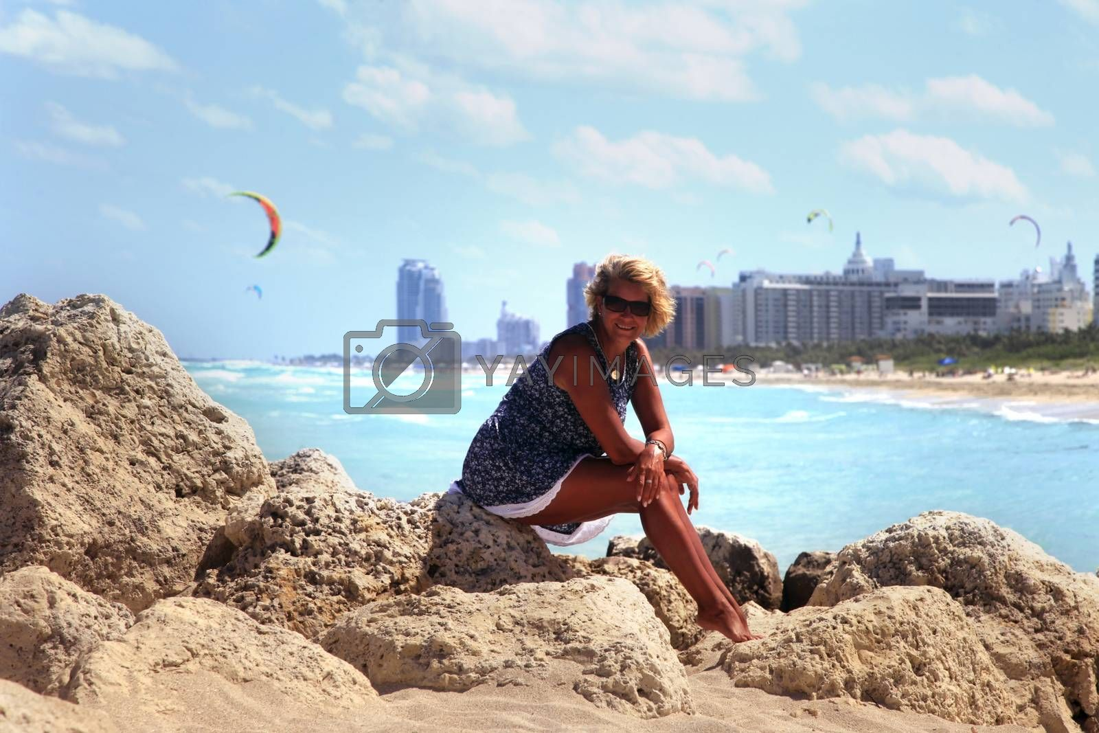 The girl sits on a stone against the backdrop of Miami Beach