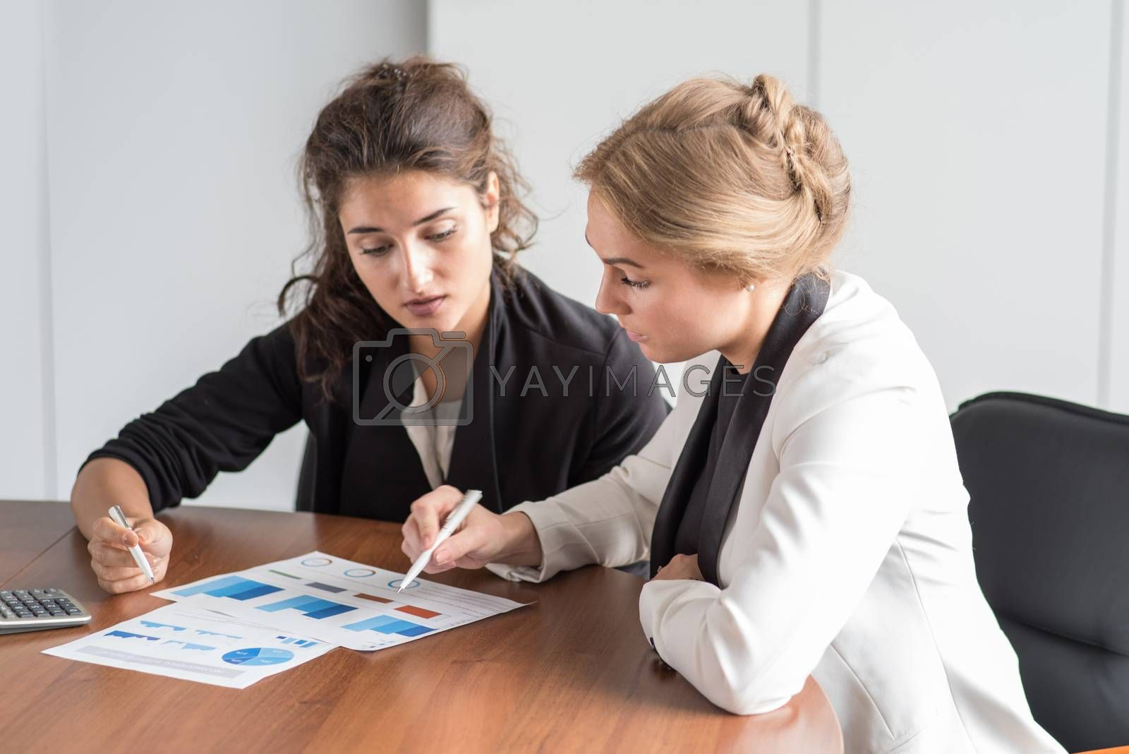 Business women working with financial diagrams, discussing financial reports at workplace
