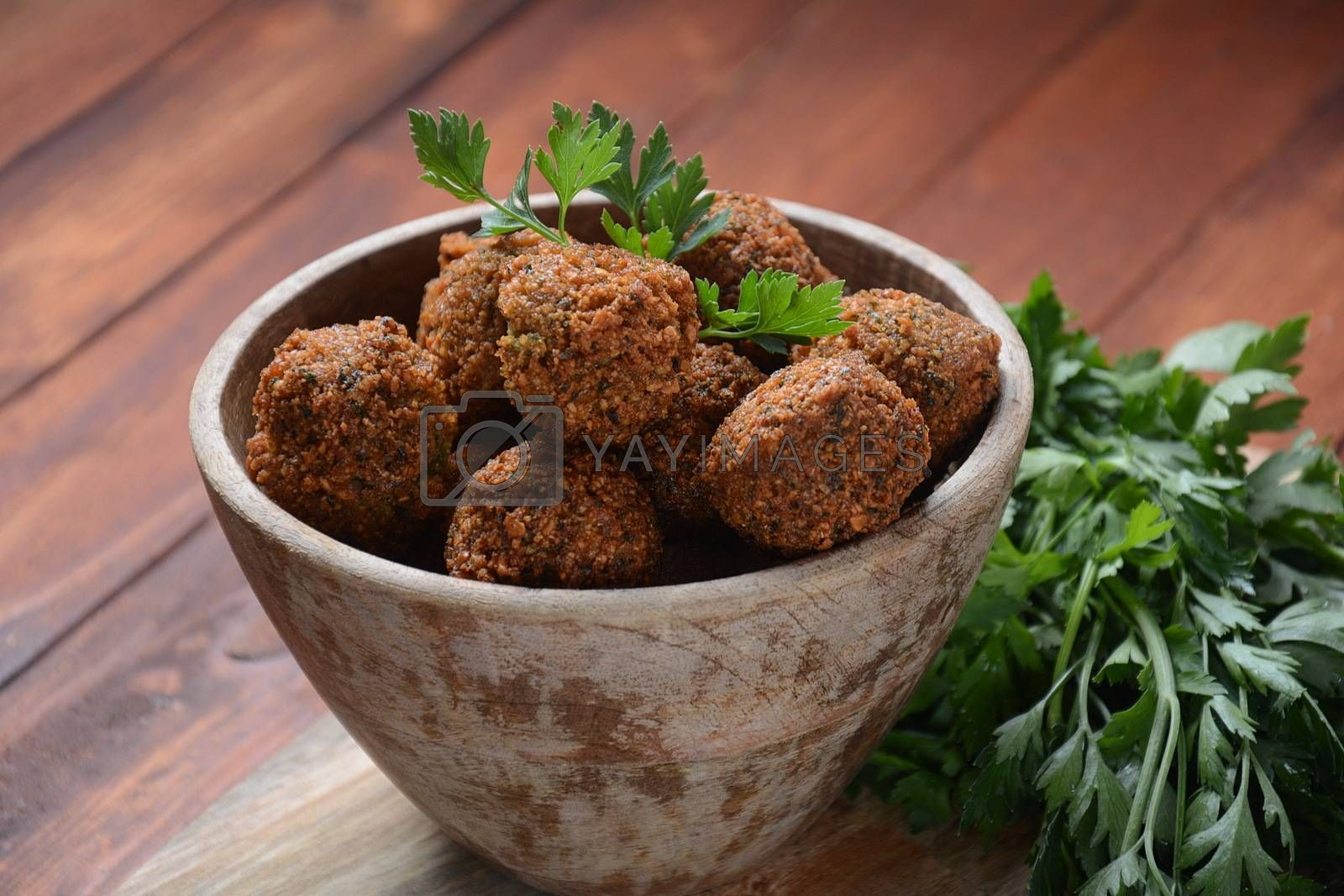 Falafel balls with parsley in wooden bowl . Vegan healthy food